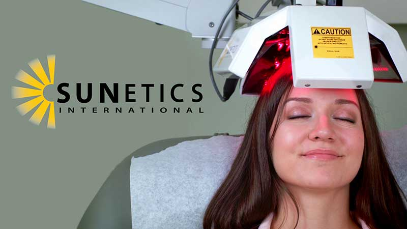 Smiling woman under the sunetics laser feeling the cool light